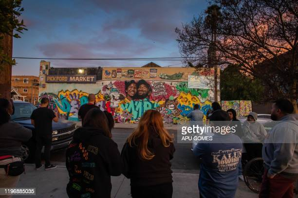 People gather in front of a mural by the artists Muck Rock and Mr79lts showing Kobe Bryant and his daughter Gianna Bryant who were killed with seven...
