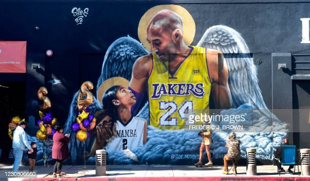 People gather in front of a mural of former Los Angeles Laker Kobe Bryant and his daughter Gianna, both with a set of wings, by artist sloe_motions...