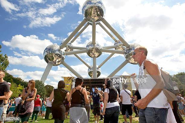 People gather in front of a stage for the 'Axe City Parade' electronic dance music festival on August 21 near the Atomium at the Heysel in Brussels...