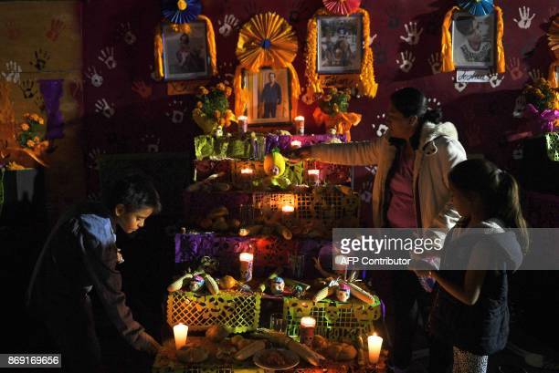 People gather in front of an altar in honour of the victims of Mexico's September 19 earthquake in the site of a collapsed building at Tlalpan...