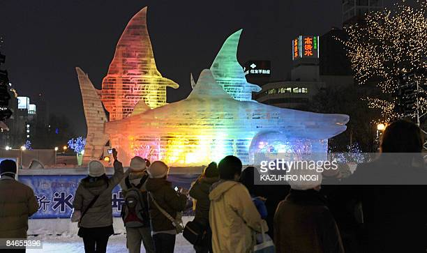 People gather in front of an ice sculpture entitled Friends in the Southern Ocean at the 60th Sapporo Snow Festival at Odori Park in central Sapporo...