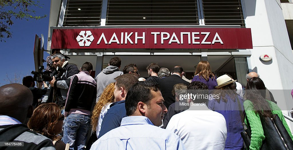 People gather in front of Laiki (Popula) Bank as the country's banks re-open following 12 days of closure on March 28, 2013 in Nicosia, Cyprus. Bank trading began again after the government negotiated a EUR 10bn (GBP 8.4bn) bailout package. Captial controls are limiting withdrawals to EUR 300 perday and the Cyprus stock excahnge remains closed.