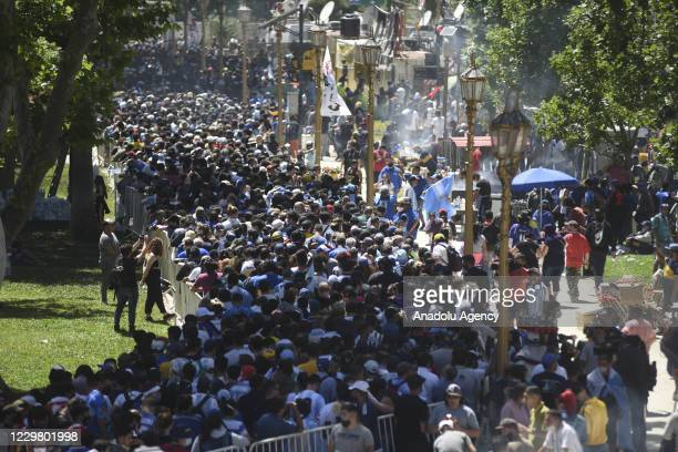 """People gather in front of the Argentinian Presidency building """"Casa Rosada"""" to attend the funeral ceremony of Diego Armando Maradona in Buenos Aires,..."""
