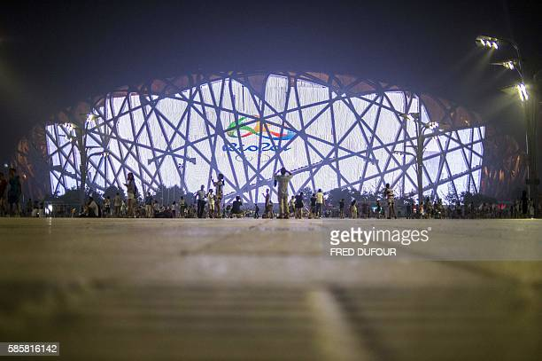People gather in front of the Beijing National Stadium also known as the Bird's Nest which is animated with the official 2016 Olympic Games teaser in...