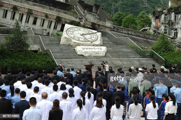 People gather in front of the destroyed Xuankou Middle School now the memorial site for the 2008 Sichuan earthquake as they pay respects for the...