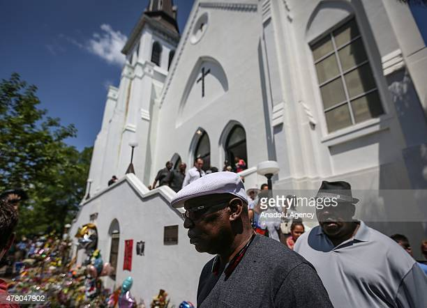 People gather in front of the Emanuel AME Church to attend the first mass after the gunman shooting attack, left nine dead on June 21 in Charleston,...