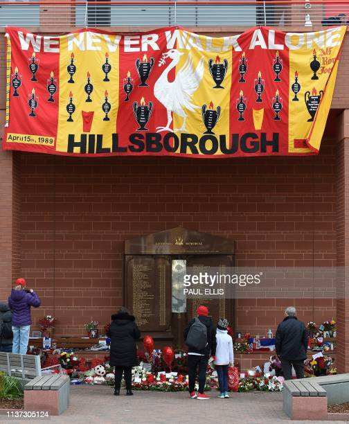 People gather in front of the Hillsborough memorial outside of Liverpool Football Club's main stand at Anfield in Liverpool northwest England on...