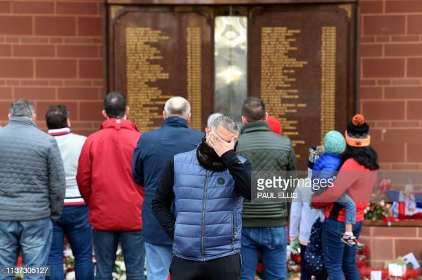 TOPSHOT People gather in front of the Hillsborough memorial outside of Liverpool Football Club's main stand at Anfield in Liverpool northwest England...