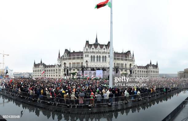 TOPSHOT People gather in front of the Hungarian Parliament as Hungarian Prime Minister Viktor Orban delivers a speech in Budapest on March 15 during...