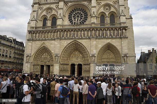 People gather in front of the Notre Dame Cathedral during a Mass led by the archbishop of Paris to pay tribute to the priest Jacques Hamel killed on...