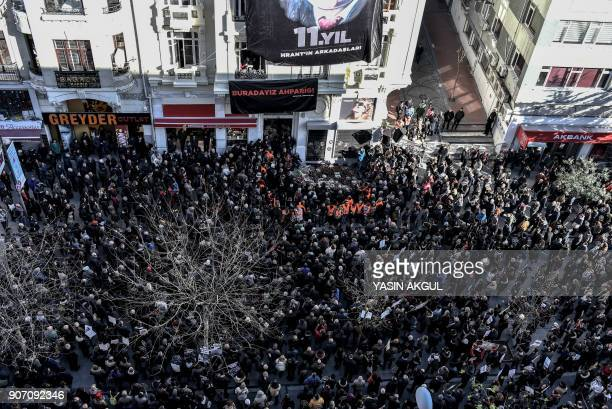 People gather in front of the offices of Armenian weekly newspaper 'Agos' during a rally commemorating 11th anniversary of the assassination of...