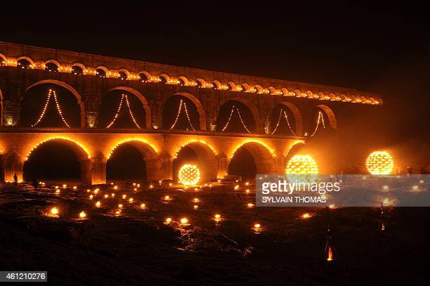 People gather in front of the Pont du Gard decorated with lights during the 'Nuit des Lucioles', an event to celebrate the 30th anniversary of the...