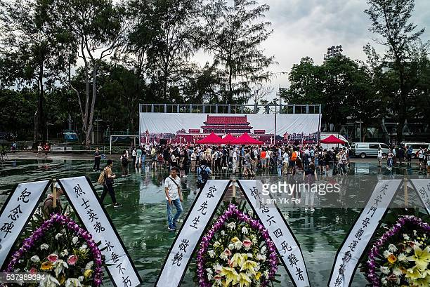 People gather in front of the poster of Tiananman Square at Victoria Park before the candlelight vigil on June 4, 2016 in Hong Kong, Hong Kong....
