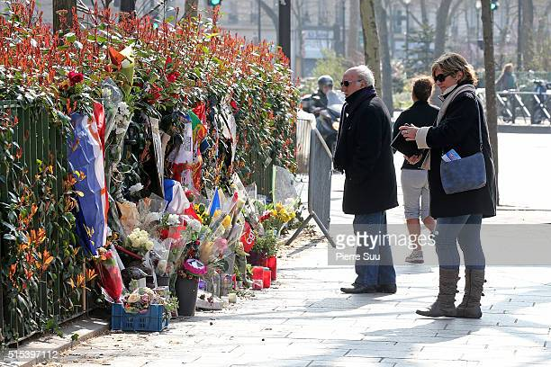 People gather in front of the tributes to the victims of the Paris attacks across the road from the Bataclan Cafe on March 13 2016 in Paris France...