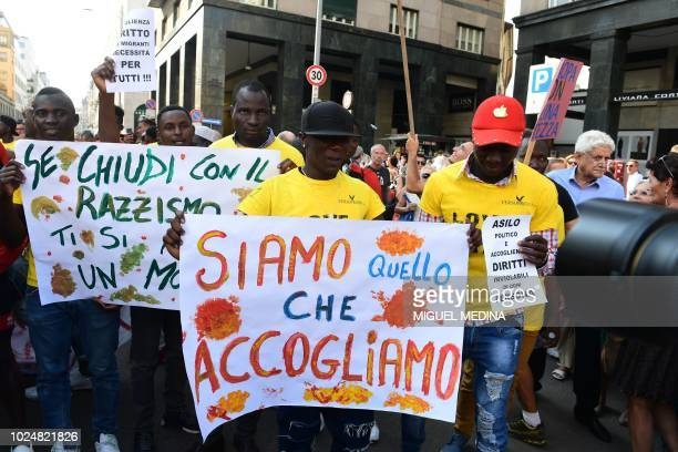People gather in Piazza San Babila as they hold banners reading We are what we welcome and If you finish with racism the world will open for you in...