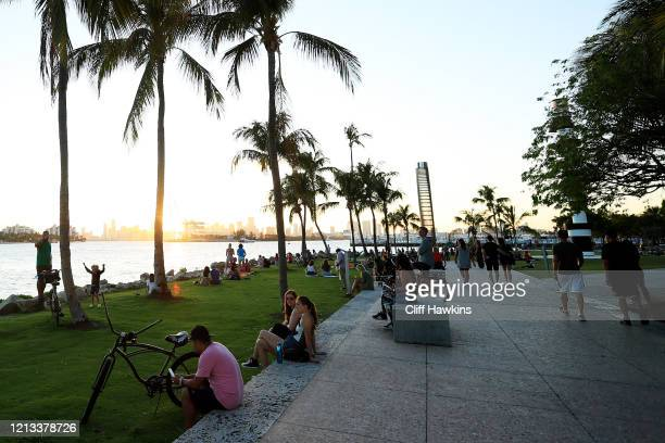 People gather in South Pointe Park at sunset on March 18 2020 in Miami Beach Florida Miami Beach city officials closed the area of the beach that is...