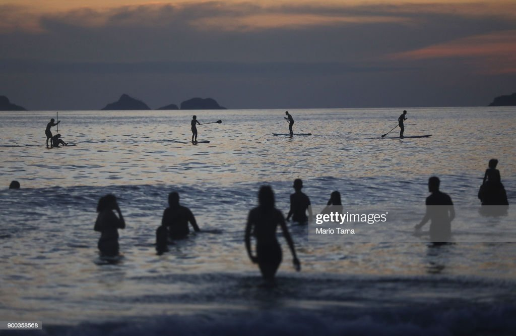 People gather in the Atlantic ocean during the first sunset of 2018 along Ipanema beach on January 1, 2018 in Rio de Janeiro, Brazil. Fireworks were launched in Rio and cities worldwide at midnight to ring in 2018.
