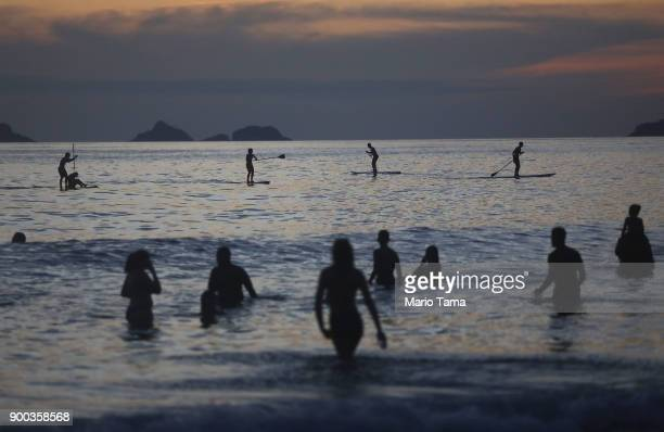 People gather in the Atlantic ocean during the first sunset of 2018 along Ipanema beach on January 1 2018 in Rio de Janeiro Brazil Fireworks were...