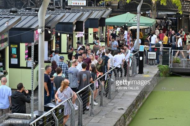 People gather in the food market in Camden in central London on September 13 the day before the UK government brings in tightened coronavirus...