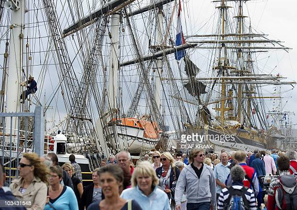 People gather in the harbor of IJmuiden on August 18 2010 to watch the sailboats participating in Sail 2010 The tall ships large vessels with...