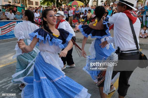 People gather in the main square watching a group of Paisa dancers dressed in traditional costumes perform during the 'Festival of Paisa Ancestor' on...