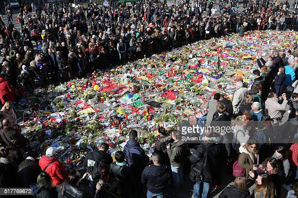 People gather in the Place de la Bourse to pay tribute to the 31 victims of the attacks in Brussels last week on March 27 2016 in Brussels Belgium...