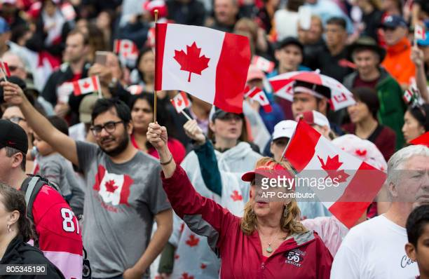 People gather in the rain to celebrate Canada's 150th birthday on Parliament Hill in Ottawa on July 1 2017 Britain's Prince Charles and his wife...