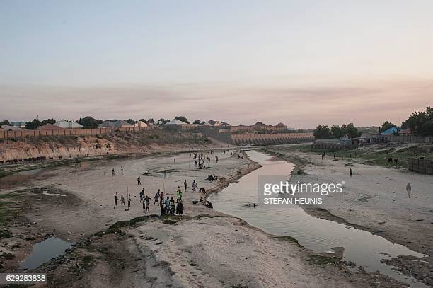People gather in the seasonal Ngadda River that flows towards Lake Chad during the rainy season in Maiduguri in northeastern Nigeria on December 6...
