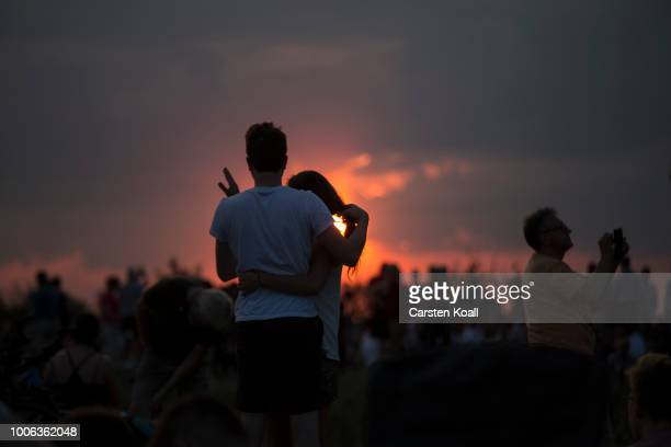 People gather in the sunset to await the rising of the blood Moon in on July 27 2018 in Berlin Germany The period of totality during this eclipse...