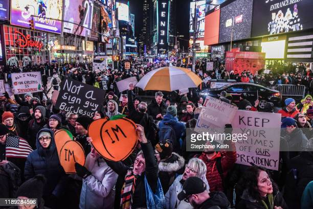 People gather in Times Square while participating in a protest in support of US President Donald Trump's potential impeachment on December 17 2019 in...