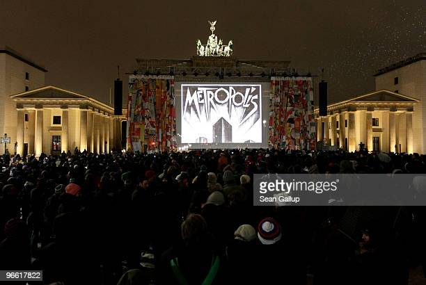 People gather in winter cold to view a screening of Fritz Lang's 'Metropolis' at the Brandenburg Gate as part of the 60th Berlinale International...