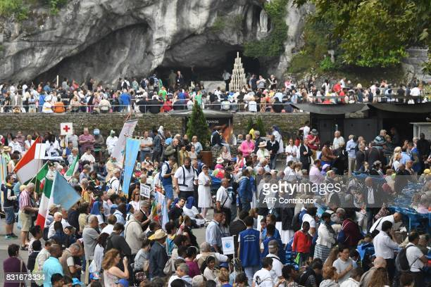 People gather inside the sanctuary of Notre Dame de Lourdes during the annual Catholic pilgrimage of Lourdes on August 15 2017 / AFP PHOTO / PASCAL...