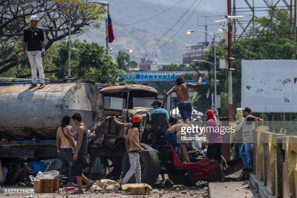 People gather near a destroyed truck on the Simon Bolivar International Bridge near the border with Venezuela in Cucuta Colombia on Sunday Feb 24...