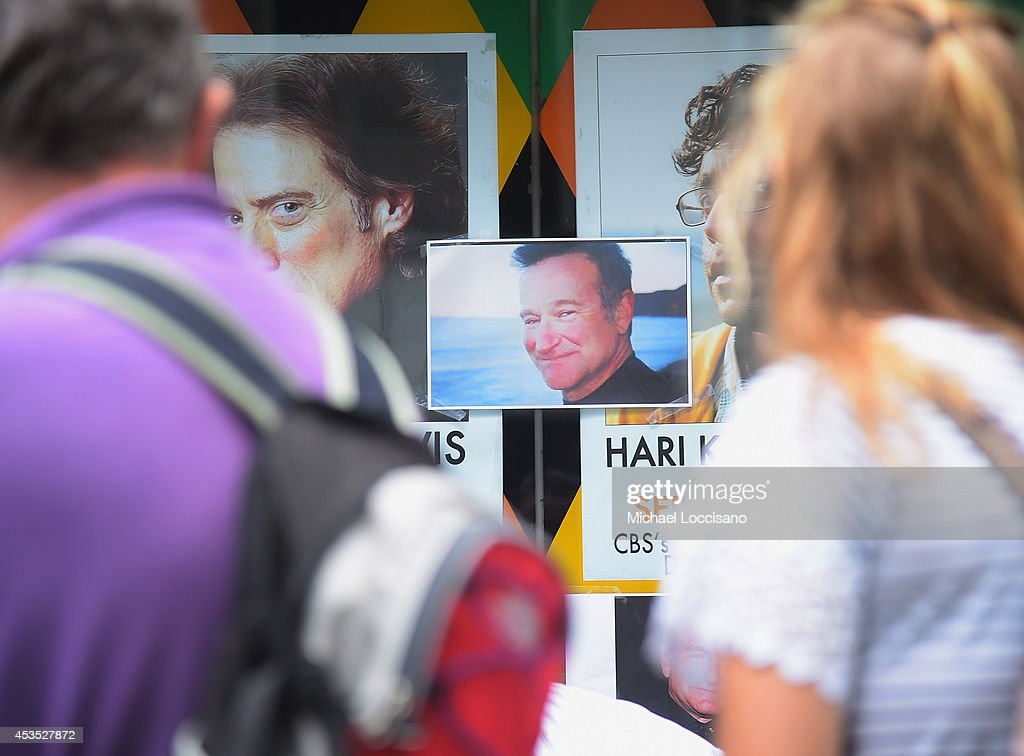 People gather near a makeshift memorial for Robin Williams in front of Carolines on Broadway comedy club on August 12, 2014 in New York City. Williams died after hanging himslef on August 11, 2014 at his home in Tiburon, California.