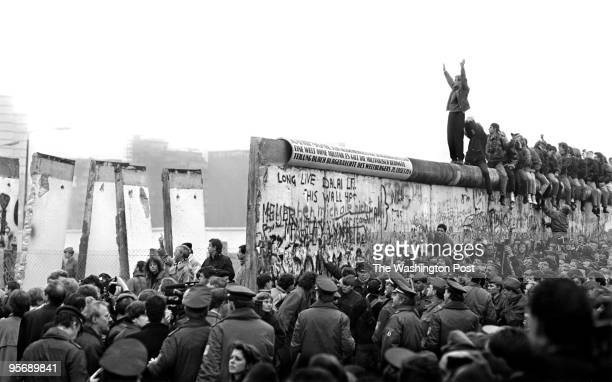 People gather near a part of the Berlin Wall that has been broken down after the communist German Democratic Republic's decision to open borders...