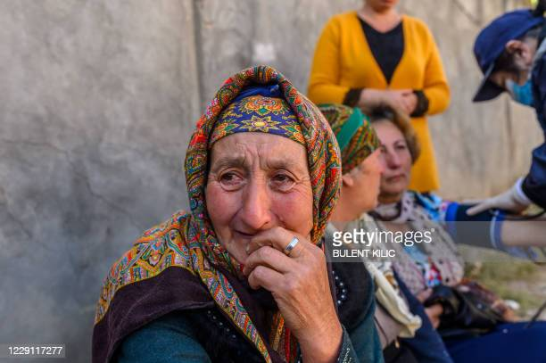 People gather near a site hit by a rocket during fighting over the breakaway region of Nagorno-Karabakh, in the city of Ganja, Azerbaijan early on...