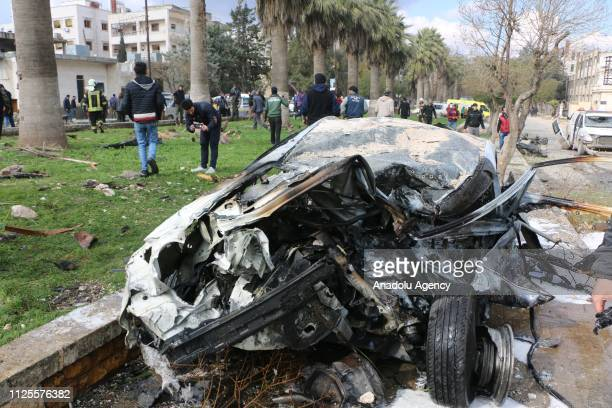 People gather near the damaged car after the consecutive bomb attacks with two bombladen vehicles in Idlib city centre Syria on February 18 2019 Nine...