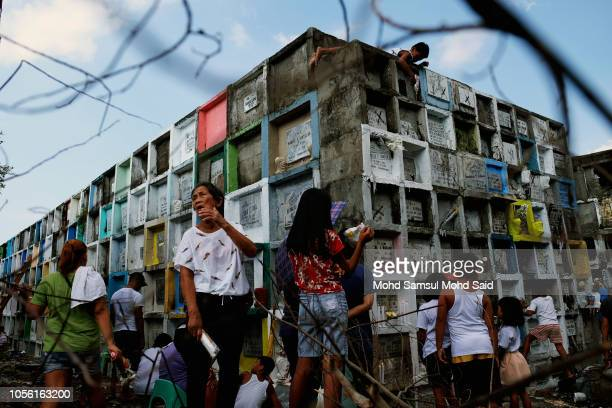 People gather near the graves of their relatives in a cemetery during the commemoration of All Saints' Day in Manila on November 1 2018 in Manila...