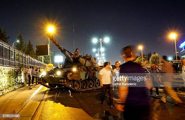 People gather near the Turkish army's tank near Ataturk Airport on July 16 2016 in Istanbul Turkey Istanbul's bridges across the Bosphorus the strait...