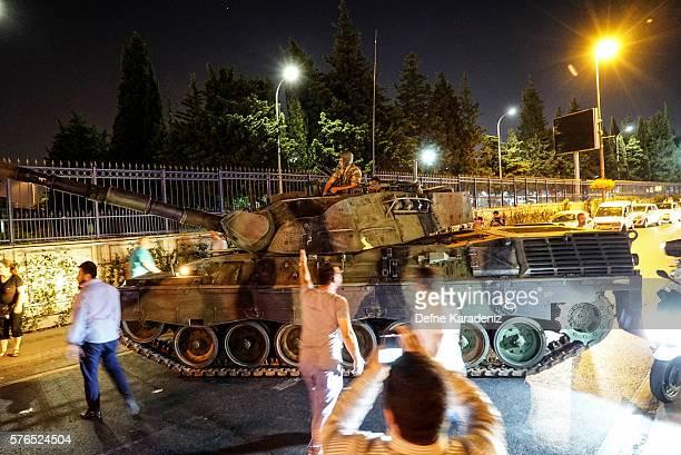 People gather near the Turkish army's tank near Ataturk Airport on July 16 2016 in Istanbul Turkey Istanbul's bridges across the Bosphorus the strait...