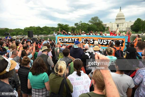People gather near the US Capitol for the People's Climate Movement before marching to the White House to protest President Donald Trump's...