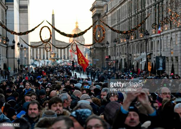 People gather near to La Madeleine church in Paris on December 9 for the procession of the funeral ceremony for beloved rock star Johnny Hallyday...