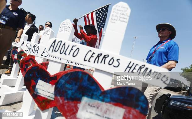 People gather near white handmade crosses memorializing the victims of a mass shooting which left at least 22 people dead on August 5 2019 in El Paso...
