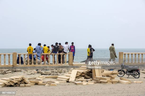 People gather next to construction materials for a sidewalk on Marine Drive in Gwadar Balochistan Pakistan on Tuesday July 4 2018 What used to be a...