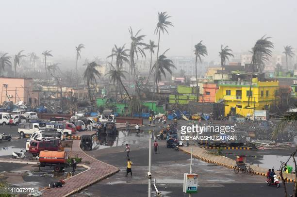 TOPSHOT People gather next to stormdamaged buildings and palm trees in Puri in the eastern Indian state of Odisha on May 4 after Cyclone Fani swept...