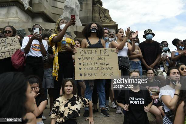 People gather next to the statue of Christopher Columbus during a demonstration in Barcelona on June 14 as part of the worldwide protests against...