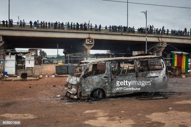 People gather on a bridge in front of a burnt vehicle on the site of an explosion in Accra on October 8 2017 a day after a gas tanker caught fire...