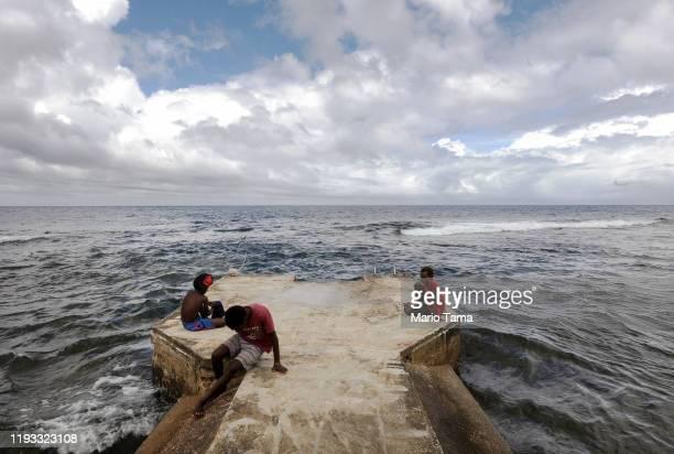 People gather on a pier on December 06 2019 in Tanna Vanuatu Satellite data show sea level has risen about 6mm per year around Vanuatu since 1993 a...