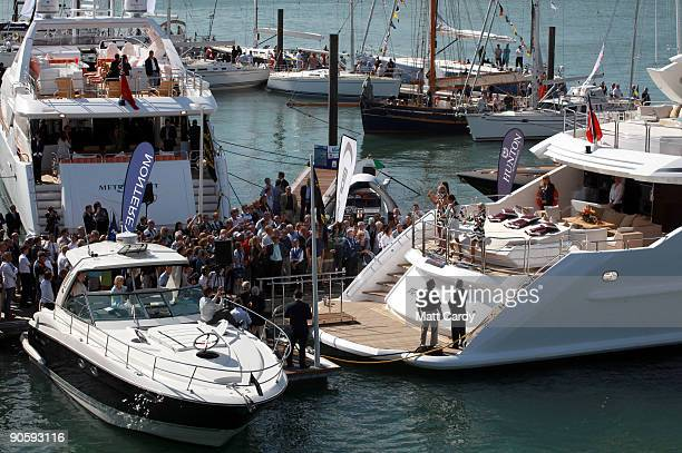 People gather on a pontoon to watch the official launch of the new Sunseeker yacht the Predator 130 which is on display on the first day of the PSP...