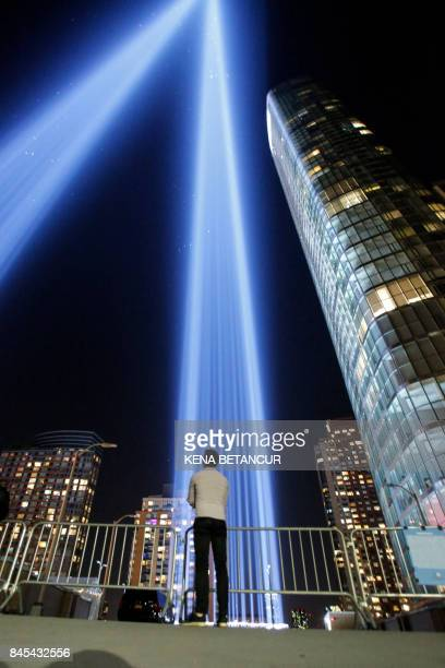 People gather on a rooftop as the 'Tribute in Light' illuminates the night sky on September 10 2017 in New York City on the eve of the anniversary of...
